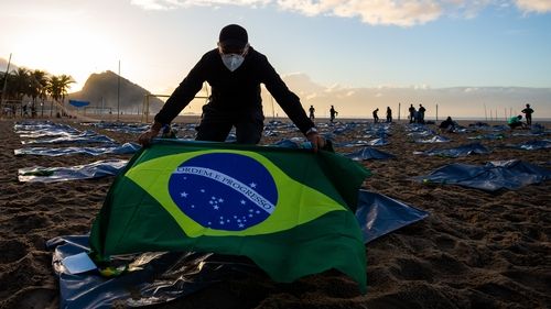 An NGO member prepares an event to pay homage to the 400,000 people to have died with Covid-19 at Copacabana beach