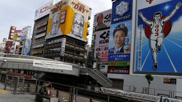 A man wearing a mask sits a bench at almost empty Dotonbori, one of Osaka's most popular tourist areas