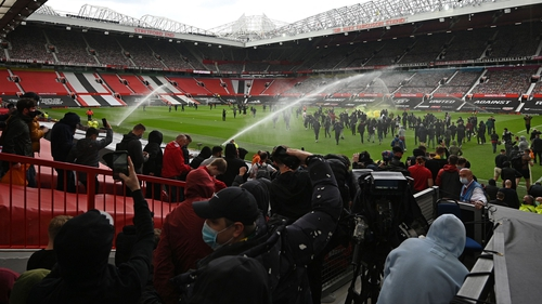 Supporters stream on to the Old Trafford pitch