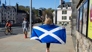 A woma walks with her towel featuring the saltire design of the national flag of Scotland outside the Scottish Parliament at Holyrood, Edinburgh, U.K.