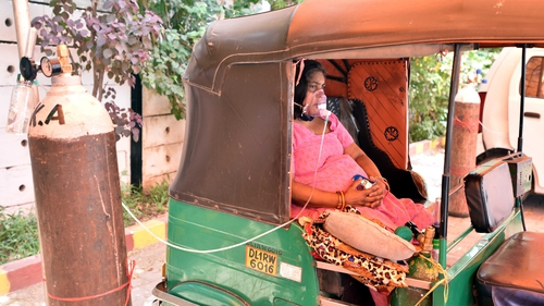 A woman with Covid-19 receives oxygen as she sits in a rickshaw in New Delhi
