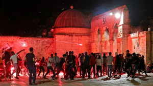 Palestinian protesters hurl flares amid clashes with Israeli security forces at the al-Aqsa mosque