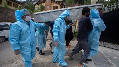 Relatives of Covid-19 victim wear protective clothing during a funeral procession in Srinagar
