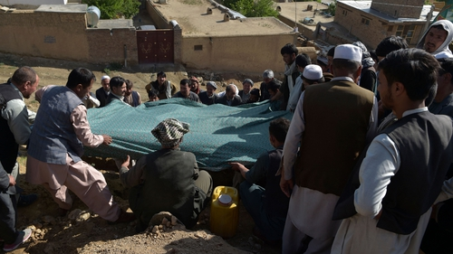 Shiite mourners lower the body of a girl, who died in yesterday's school blast, at a cemetery in Kabul