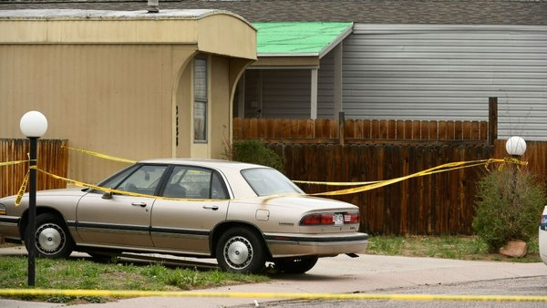 Police tape covers cars and lights along the street at the scene of an overnight shooting in the Canterbury Mobile Home Park