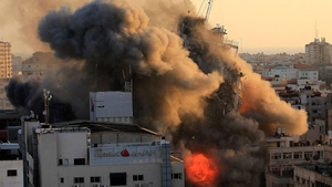 Heavy smoke and fire surround Al-Sharouk tower in Gaza City as it collapses during an Israeli air strike