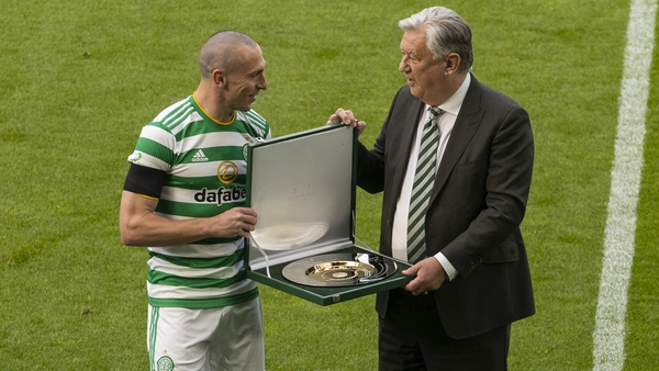 Celtic chief executive Peter Lawwell (R) presents Scott Brown with a commemorative silver plate