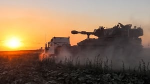 An Israeli tank, loaded on a trailer, at the Gaza border