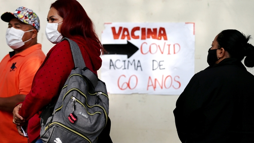 People wait outside a Covid-19 vaccine clinic at a public health centre in Sao Paulo