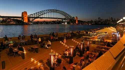 Crowds fill bars and restaurants along the Sydney Opera House forecourt at Circular Quay in Sydney