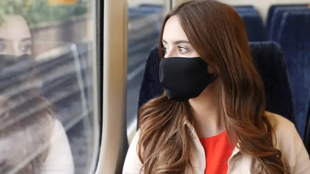 woman on a train wearing a mask
