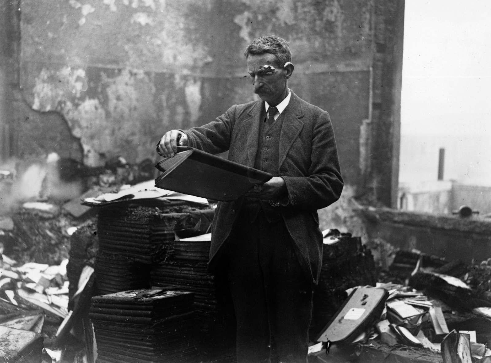 Image - A civil servant retrieves files from the destroyed building. Credit: Getty Images.