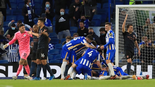 Dan Burn is mobbed by his Brighton team-mates after scoring the winning goal at the Amex