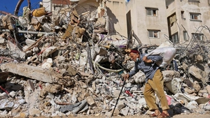 A man walks past a building destroyed by Israeli bombardment in Gaza City