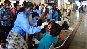 Healthcare workers collect nasal samples from passengers at CSMT station in Mumbai, India