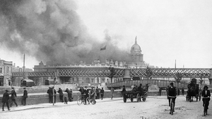 Dubliners watch on from across the Liffey as the Custom House burns after the IRA attack in May 1921. Photo: Bettmann/Getty Images