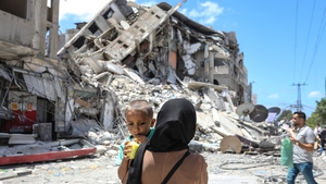 A Palestinian woman carries her baby near the rubble of Al Shorouq tower in Gaza