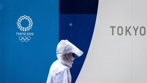 A pedestrian walks past a 2020 Olympic and Paralympic Games logo on a decoration board in Tokyo