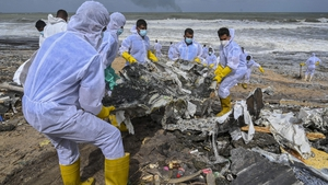 Members of the Sri Lankan navy work to remove debris washed ashore