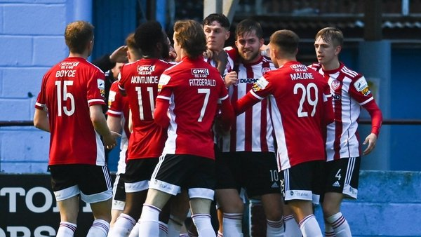 Will Patching is mobbed by his team-mates after scoring his and Derry's second goal of the night