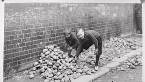 Children gather stones on the streets of Belfast, circa 1920. Photo: Getty Images