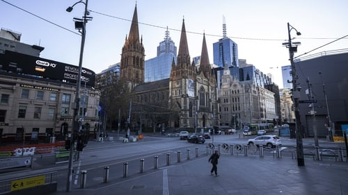 A person walks along a very quiet Flinders Street in Melbourne