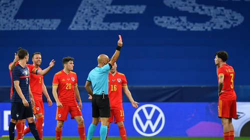 Referee Luis Godinho brandishes a red card after adjudging that Neco Williams had handled the ball deliberately
