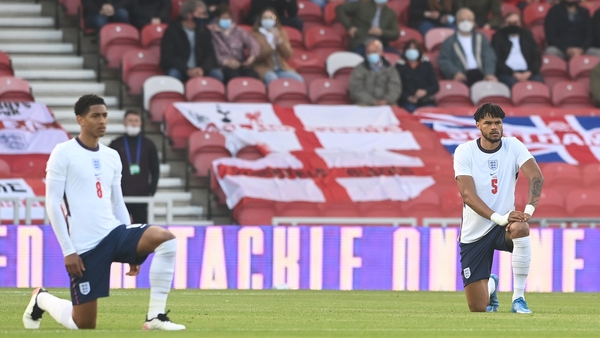 Jude Bellingham and Tyrone Mings take the knee ahead of the friendly against Austria