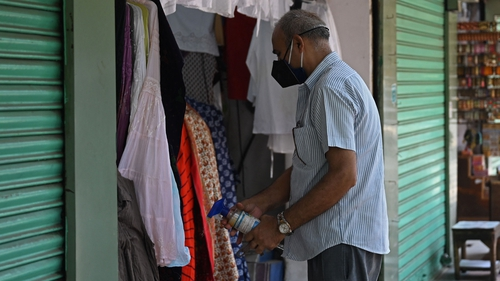 A shopkeeper in New Delhi gets ready to reopen his store