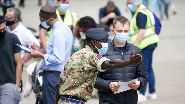 Soldiers from the Royal Horse Artillery guide members of the public at a rapid vaccination centre in Bolton