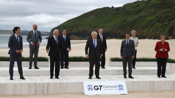 Leaders pose for a 'family' photo on the beach at Carbis Bay