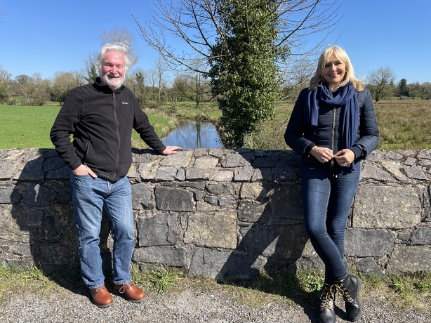 Miriam stands by a wall with darach MacDonald