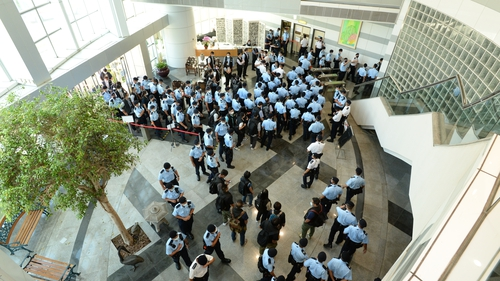 A photo made available by Apple Daily shows police officers arriving at the office of Next Media