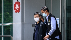 Apple Daily editor Ryan Law being escorted by Hong Kong police from the newspaper's office