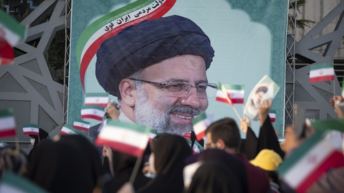Supporters wave flags in front of a giant poster of the new Iranian president
