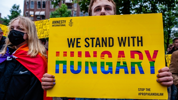 A man holds a placard during a demonstration against Hungary's Anti-LGBT Law in Amsterdam