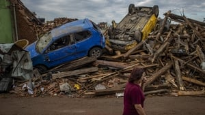 A woman walks past damaged cars after the tornado hit the village of Mikulcice