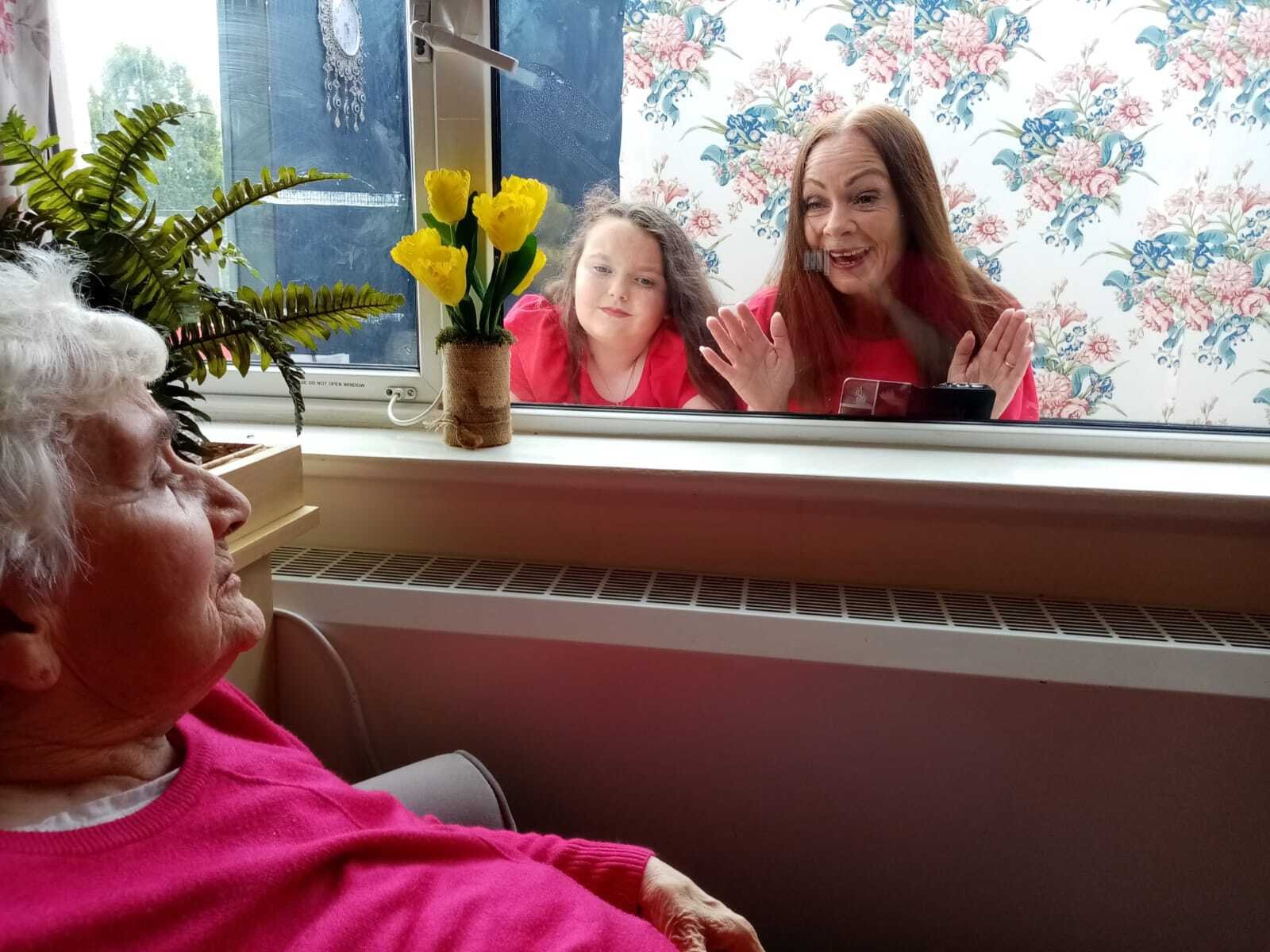 Image - Christine Thompson and her daughter, Sarah, enjoy a precious window visit with her mother, Kathleen