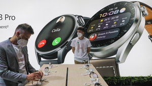 An attendee inspects Huawei smartwatches on the Huawei stand at the MWC in Barcelona