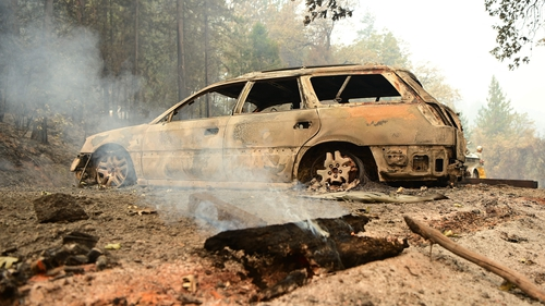 A log smoulders in front of a burnt car at Shasta Lake, California