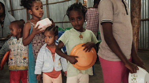 Children, who fled the violence in Ethiopia's, Tigray region, wait in line for