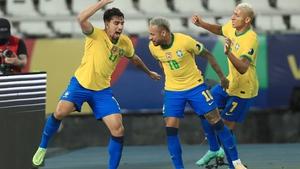 Lucas Paqueta (L) celebrates with team-mates Neymar Jr (C) and Richarlison after scoring for Brazil against Peru