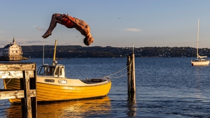 A man somersaults into the fjord for an evening swim on Lindoya island in Oslo