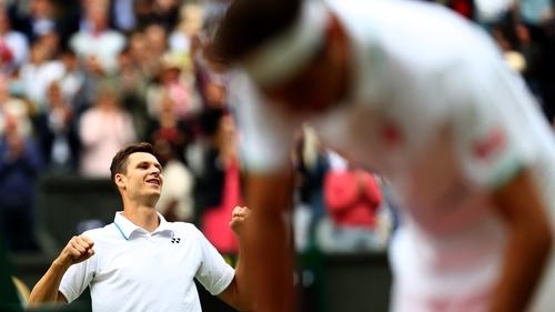 Hubert Hurkacz celebrates while Roger Federer slumps in the foreground