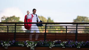 Roger Federer waves to fans as he walks across the players bridge at Wimbledon