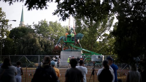 Onlookers cheered as the statue was put on a truck and driven away