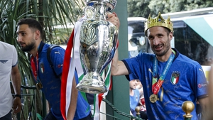 Italy's captain Giorgio Chiellini (R) carrying the trophy as his team arrives at Parco dei Principi hotel in Rome this morning