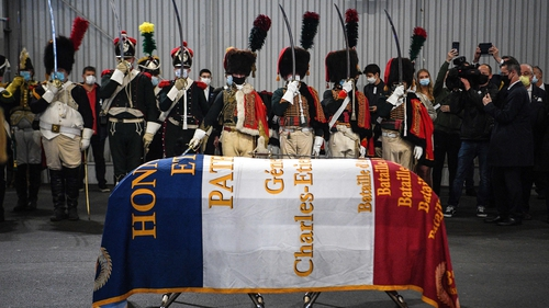 Men dressed as Napoleon-era fighters stand in respect beside a coffin containing the remains of Charles Etienne Gudin in Paris today