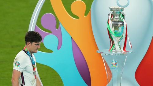 A dejected Harry Maguire walks past the Euro 2020 trophy