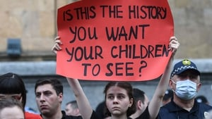 A woman holds up a placard during a rally in Tbilisi